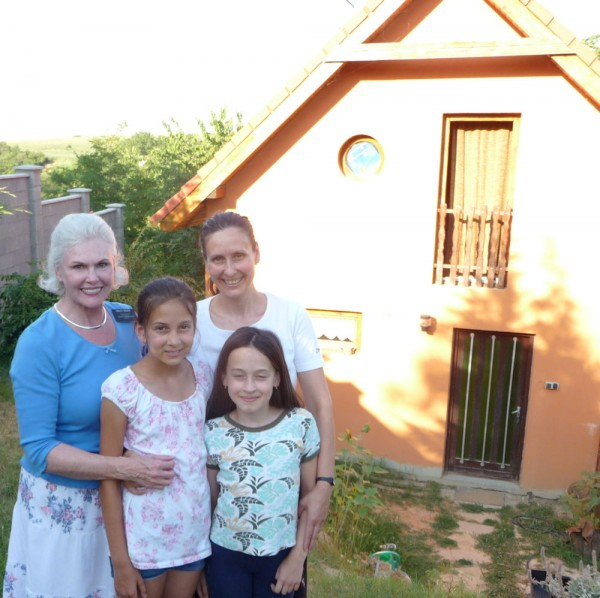 Zsuzsa and Her Daughters in Front of their Home